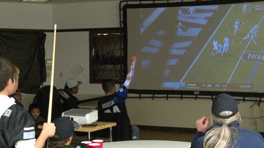 Buck (left) watches the Raiders intercept a Philip Rivers pass at Thursday's watch party.