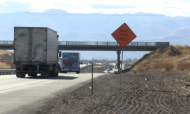 Trucks travel on I-15 near active construction.