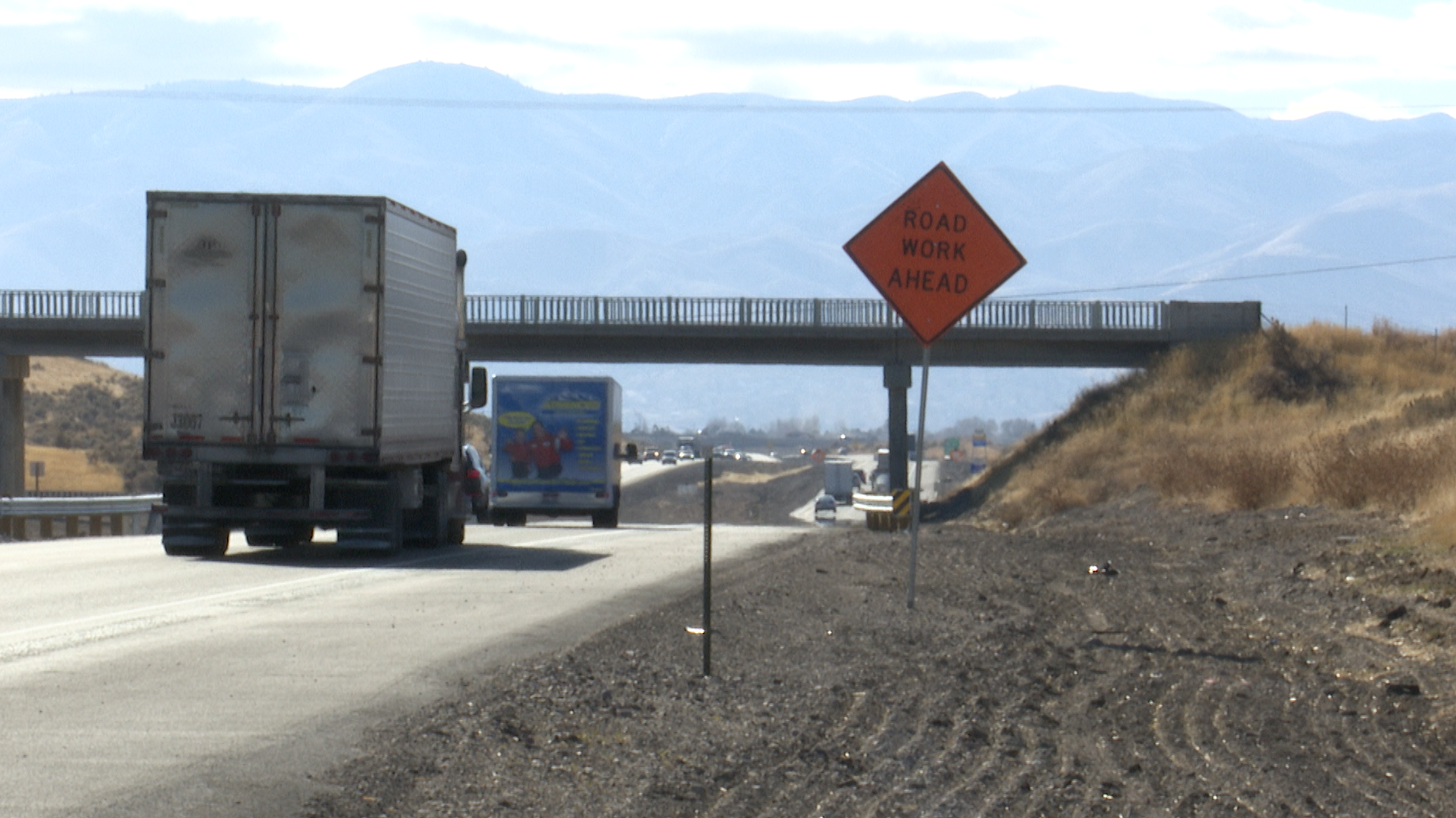 Trucks travel on I-15 near active construction.